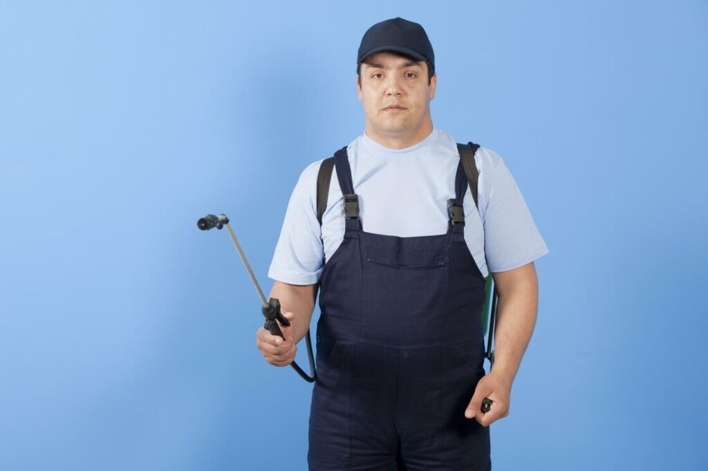 A pest controller is standing with his instrument